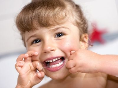 When should I start flossing my child's teeth?
